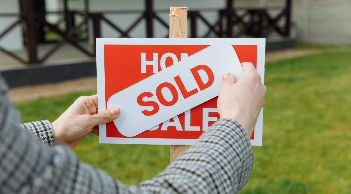 shallow focus photo of a realtor posting a sold sticker